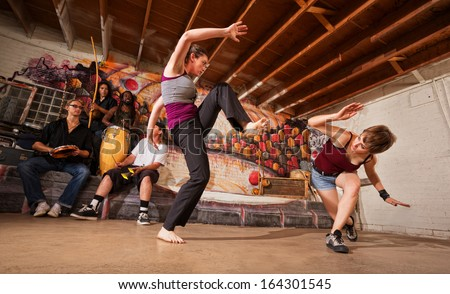 Two female capoeira performers sparring indoors while music plays