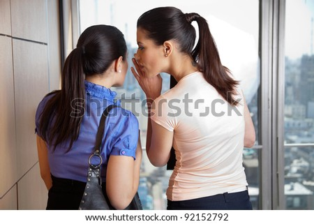 Two female co-workers whispering in office - stock photo