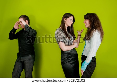 Two female colleagues gossiping and man holding his head in disbelief - stock photo