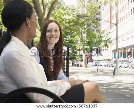 Two female colleagues talking in street