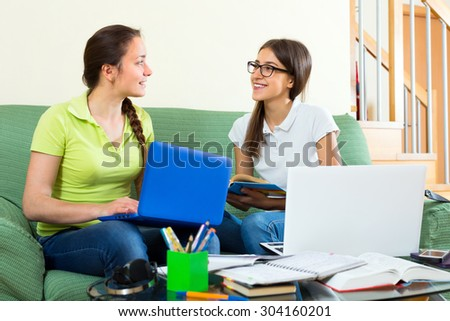 Two female college students working on laptop computers at home