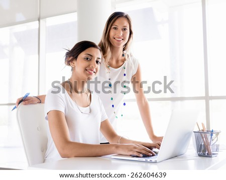 Two female collegues working together in an office - stock photo
