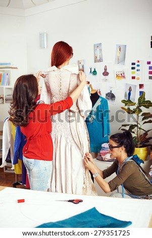 Two female designers working on a dress