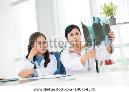 Two female doctors examining an x-ray in the clinic - stock photo