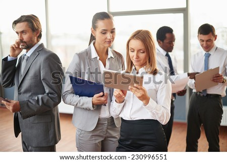 Two female employees using touchpad with several co-workers doing their job near by - stock photo