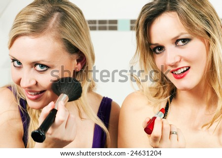 Two female friends applying lipstick and make-up with a brush - presumably to get ready for a party - stock photo