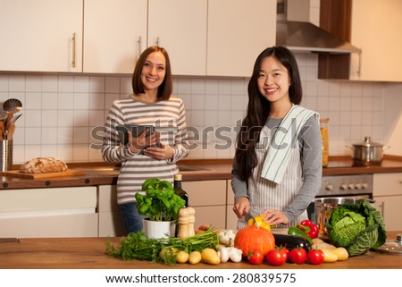 Two female friends are cooking together at home - stock photo