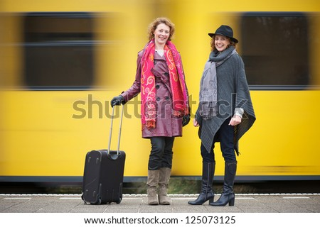 Two female friends are standing on the train station platform with luggage as a yellow train speeds past them in the background