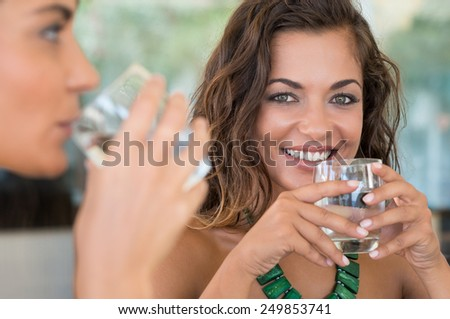 Two Female Friends Drinking Mineral Water With Glass At Bar - stock photo