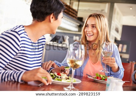 Two female friends eating at a restaurant - stock photo