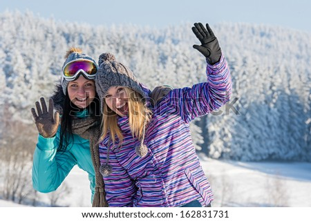 Two female friends enjoy winter snow in mountains holiday break - stock photo