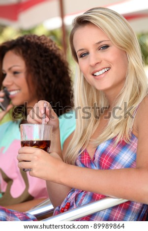 Two female friends having drink on terrace - stock photo