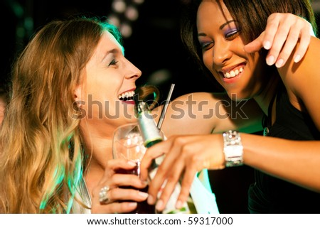 Two female friends having drinks in a bar or nightclub - stock photo