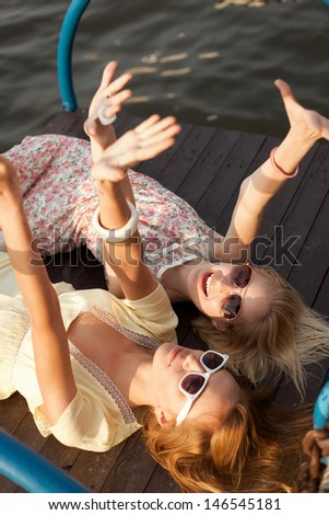 Two Female Friends having fun near the water. Outdoors, Lifestyle - stock photo