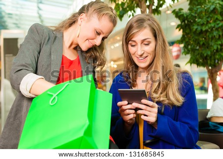 Two female friends having fun while shopping in a mall, they bought a e-book