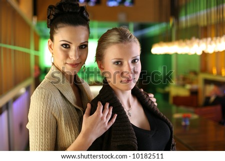 Two female friends in colorful office.