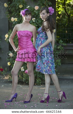 two female friends in summer dresses posing outdoor