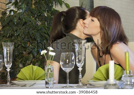 two female friends kissing each other by meeting in restaurant - stock photo
