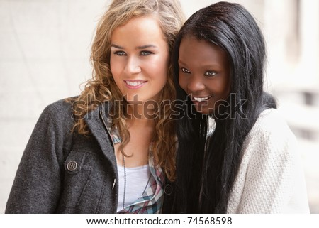 Two female friends looking at something interesting - stock photo