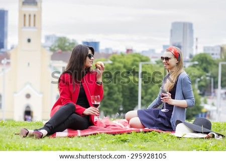 Two female friends on a picnic blanket - stock photo