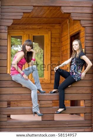 Two female friends on a veranda - stock photo