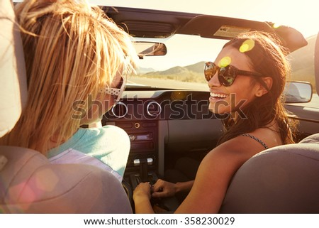 Two Female Friends On Road Trip Driving In Convertible Car - stock photo