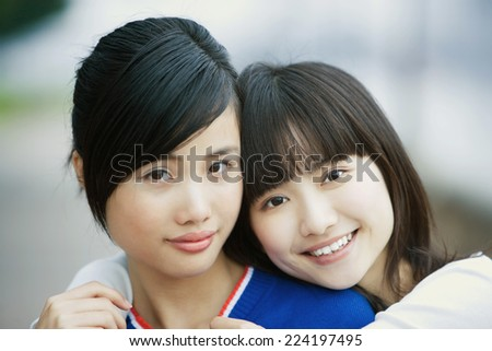 Two female friends, one with arms around the other's shoulders - stock photo