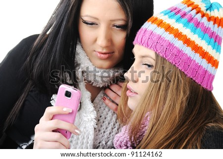 Two female friends reading sms message on cell phone