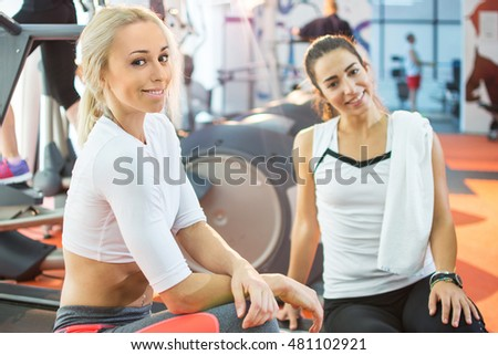 Two female friends relaxing after hard workout at gym.