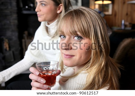 Two female friends relaxing at home with glass of wine - stock photo