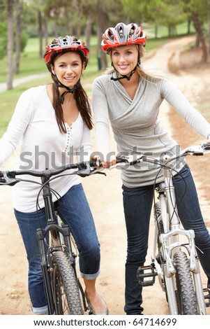 Two Female friends riding bikes in park - stock photo