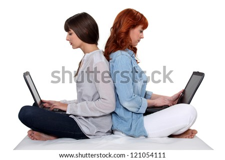 Two female friends sat back to back with laptops - stock photo
