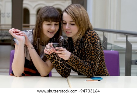 Two female friends sitting in a cafe - stock photo