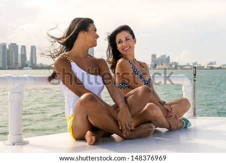Two female friends sitting on the quay in a close up shot having fun with Miami skyline behind - stock photo