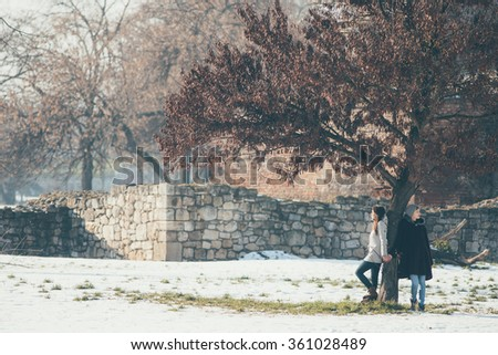 Two female friends standing beside tree holding hands - stock photo