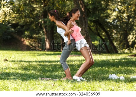 Two female friends stretching back and laughing - stock photo