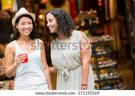 Two female friends talking and laughing in store - stock photo