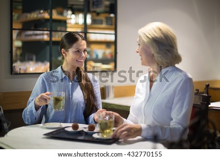 Two female friends talking at cafe and smiling - stock photo