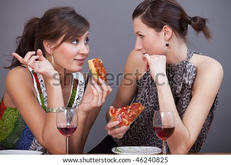 two female friends talking in studio with glasses sparkling wine and pizzas - stock photo