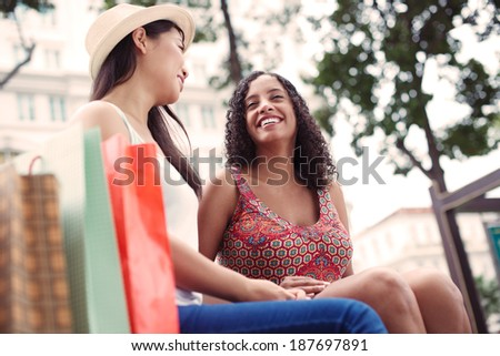 Two female friends talking outdoors - stock photo