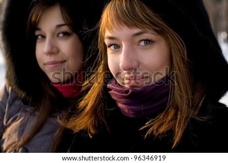 Two female friends walking in park in winter - stock photo