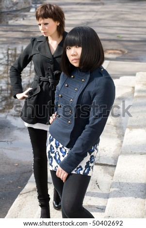 Two female friends walking outdoor - stock photo
