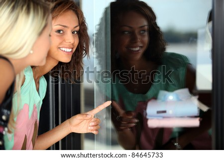 Two female friends window shopping - stock photo