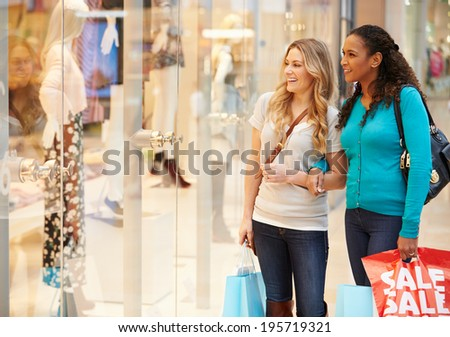 Two Female Friends Window Shopping With Bags