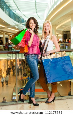 Two female friends with shopping bags having fun while shopping in a mall - stock photo