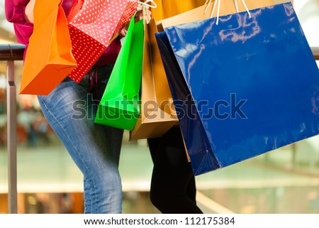 Two female friends with shopping bags having fun while shopping in a mall, close-up on bags