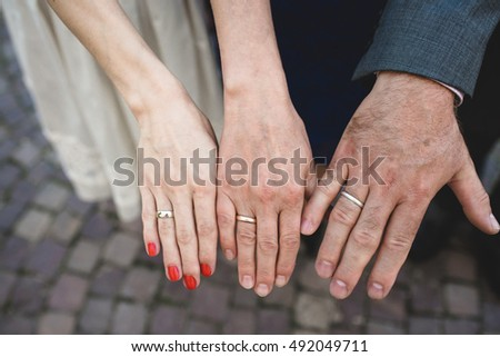 two female hands and one man's hand