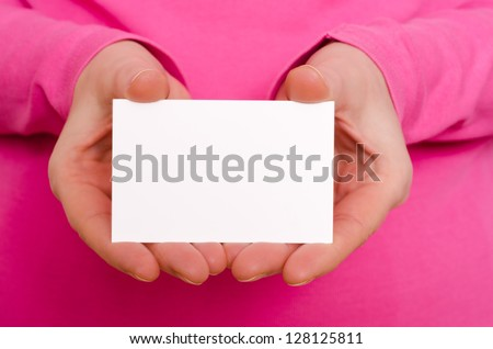 Two female hands are holding a blank business card - stock photo