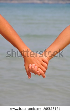 Two female hands, hand in hand,against the sea