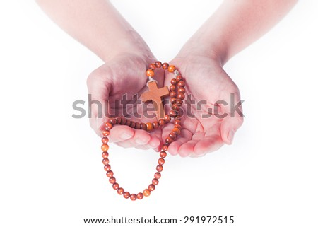 Two female hands holding brown rosary on a white background - stock photo